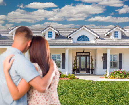 front house: Young Military Couple Facing Beautiful New House.