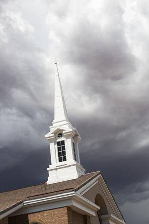 Church Steeple Tower Below Ominous Stormy Thunderstorm Clouds.