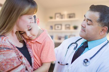 Young Sick Boy and Mother Visiting with Hispanic Doctor in Office. photo