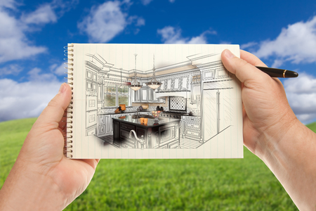 Male Hands Holding Pen and Pad of Paper Up with Custom Kitchen Illustration Outside Near Grass Field and Blue Sky.