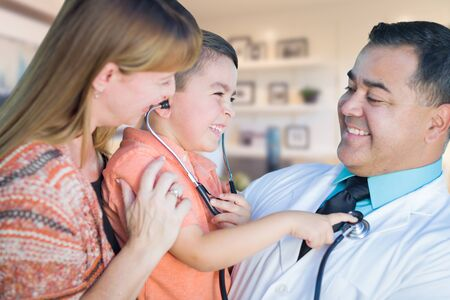 Young Boy and Mother Visiting with Hispanic Doctor in Office. photo