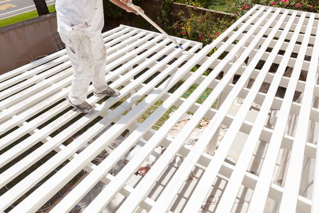 painted wood: Professional Painter Rolling White Paint Onto The Top of A Home Patio Cover.
