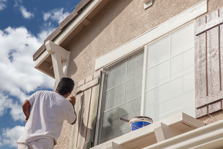 Professional House Painter Painting the Trim And Shutters of A Home. photo