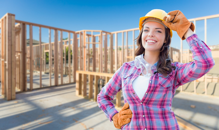 Young Attractive Female Construction Worker Wearing Gloves, Hard Hat and Protective Goggles At Construction Site. photo