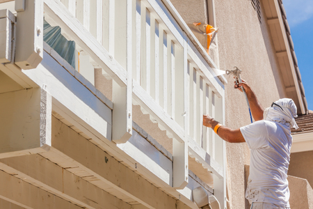 Professional House Painter Wearing Facial Protection Spray Painting Deck of A Home. photo