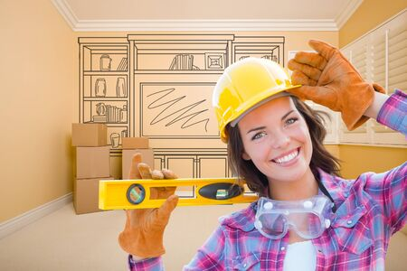 Female Construction Worker Holding Level In Front of Custom Built In Entertainment Unit Drawing in Empty Room. photo