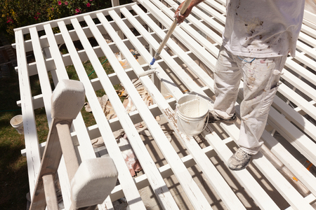 Professional Painter Rolling White Paint Onto The Top of A Home Patio Cover. photo