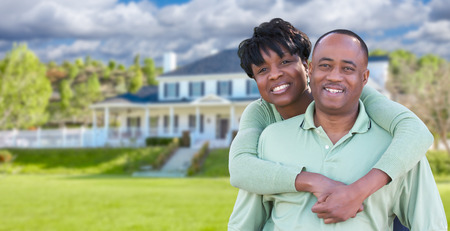 Happy African American Couple In Front of Beautiful House. Stock Photo