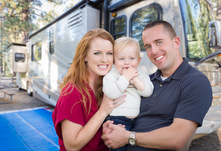 Happy Young Military Family In Front of Their Beautiful RV At The Campground.