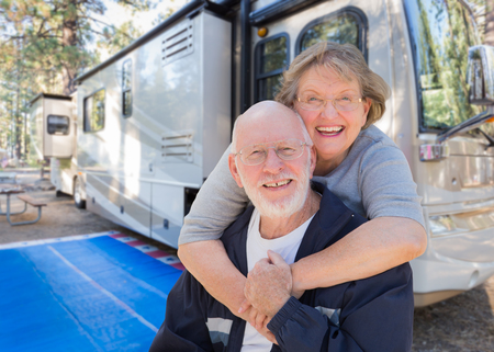 Senior Couple In Front of Their Beautiful RV At The Campground. Foto de archivo