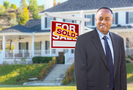 African American Agent In Front of Beautiful Custom House and Sold For Sale Real Estate Sign. Banco de Imagens
