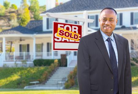 agente afroamericano di fronte a una bella casa personalizzata e venduto per il commercio immobiliare Archivio Fotografico