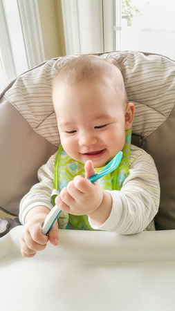 Adorable Chinese and Caucasian Baby Boy Playing With His Spoon Sitting in High Chair.