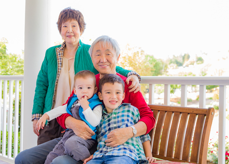 Senior Adult Chinese Couple Sitting With Their Mixed Race Grandchildren Stock fotó