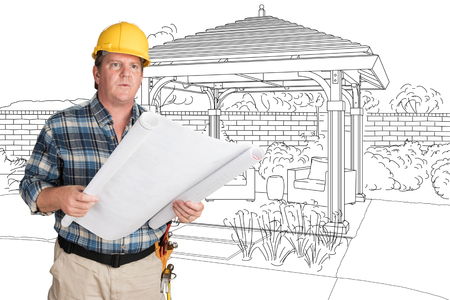 Male Contractor With House Plans Wearing Hard Hat In Front of Custom Pergola Patio Covering Drawing Imagens