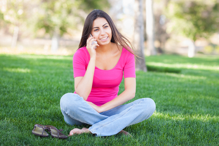 Beautiful Young Ethnic Woman Talking on Her Smartphone Outside.
