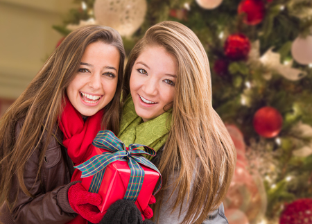 Mixed Race Young Adult Females Holding A Christmas Gift In Front Of Decorated Tree
