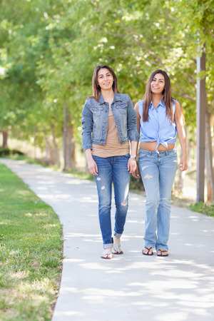 identical: Two Beautiful Ethnic Twin Sisters Walking Outdoors.