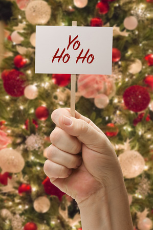 Hand Holding Yo Ho Ho Card In Front of Decorated Christmas Tree.
