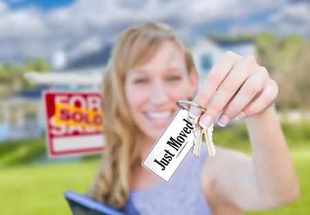 Woman Holding New House Keys with Just Moved Card In Front of Sold Real Estate Sign and Home.