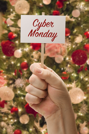hand holding cyber monday card in front of decorated christmas tree stock photo 92706458