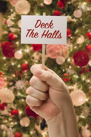 Hand Holding Deck The Halls Card In Front of Decorated Christmas Tree. Standard-Bild