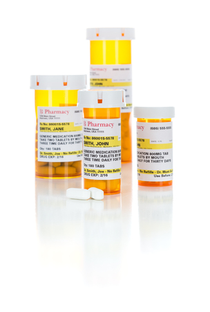 Non-Proprietary Medicine Prescription Bottles and Pills Isolated on a White Background.