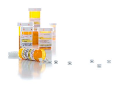 Nicht-proprietäre Medizin-Verordnungs-Flaschen und verschüttete Pillen lokalisiert auf einem weißen Hintergrund.