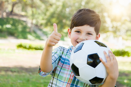 Cute Young Boy Playing with Soccer Ball and Thumbs Up Outdoors in the Park.
