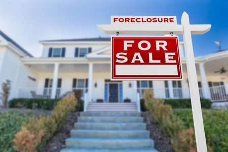 Left Facing Foreclosure For Sale Real Estate Sign in Front of House.