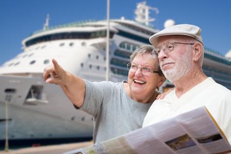 Turisti adulti senior felici delle coppie con l'opuscolo accanto alla nave da crociera del passeggero.