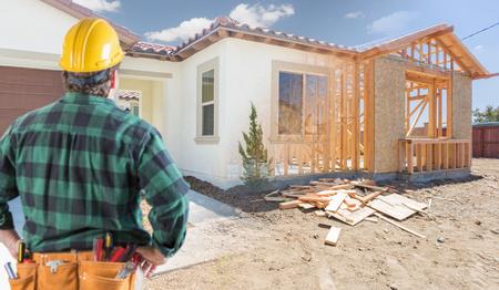 Entrepreneur debout à l'extérieur de l'encadrement de la construction et photo de la nouvelle maison.