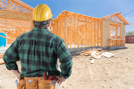 Contractor Standing Outside Construction Framing of New House. Stock Photo