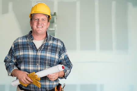 Contractor with Plans and Hard Hat In Front of Drywall.