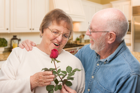 Happy Senior Adult Man Giving Red Rose to His Wife Inside Kitchen. Stockfoto - 95322958