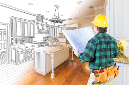 Male Contractor with Hard Hat and Plans Looking At Custom Kitchen Drawing Photo Combination On White. Stock Photo