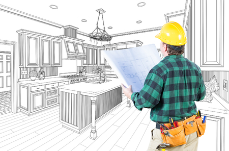Male Contractor with Hard Hat and Plans Looking At Custom Kitchen Drawing On White. Stock Photo