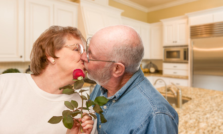 Happy Senior Adult Man Giving Red Rose to His Wife Inside Kitchen.