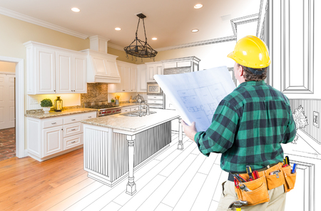 Male Contractor with Hard Hat and Plans Looking At Custom Kitchen Drawing Photo Combination On White. 스톡 콘텐츠