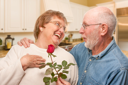 Happy Senior Adult Man Giving Red Rose to His Wife Inside Kitchen. Stockfoto - 95323011