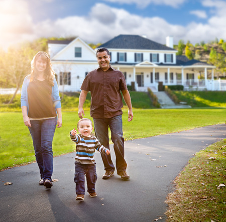 Happy Mixed Race Family Walking in Front of Beautiful Custom Home. Stock Photo