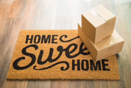 Home Sweet Home Welcome Mat On Wood Floor With Shipment of Boxes.