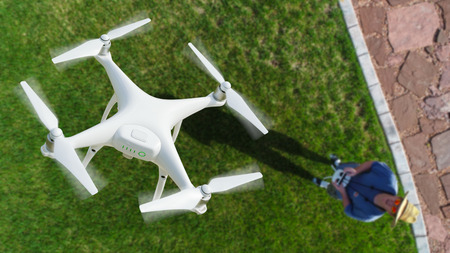 Drone Quadcopter (UAV) In Air Above Pilot With Remote Controller.