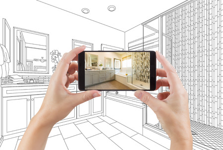 Hands Holding Smart Phone with Master Bathroom Photo on Screen and Drawing Behind. Stock Photo