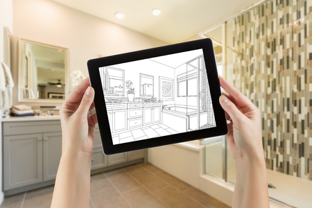 Hands Holding Computer Tablet with Master Bathroom Drawing on Screen and Photo Behind.