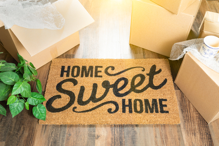 Home Sweet Home Welcome Mat and Moving Boxes on Hard Wood Floor. Reklamní fotografie