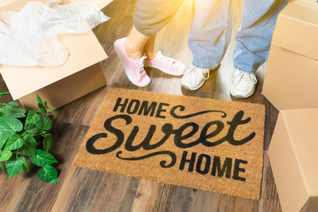Man and Woman Standing Near Home Sweet Home Welcome Mat, Moving Boxes and Plant.