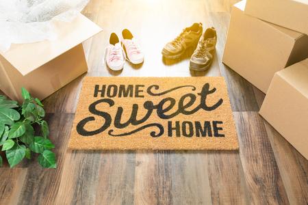 Tappeto di benvenuto per la casa dolce casa, scatole mobili, scarpe da donna e uomo e pianta su pavimenti in legno duro.