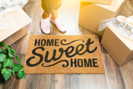 Woman in Pink Shoes and Sweats Standing Near Home Sweet Home Welcome Mat, Boxes and Plant. Banque d'images