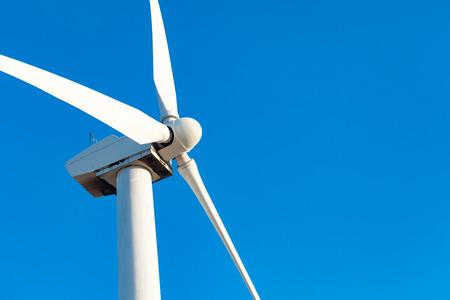 Single Wind Turbine Over Dramatic Blue Sky.